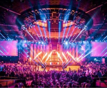 Escenario de Esports con audiencias en sus asientos y luces de colores en su presentación inicial