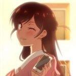 Imagen tomada de 'Kanojo Okarishimasu' con la protagonista gente a una puesta de sol de espaldas mientras mira sobre su hombro a la cámara con una sonrisa.