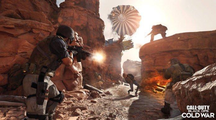 Tres soldados disparando al atardecer con fusiles a un paracaidista que tocó tierra en un cañón.