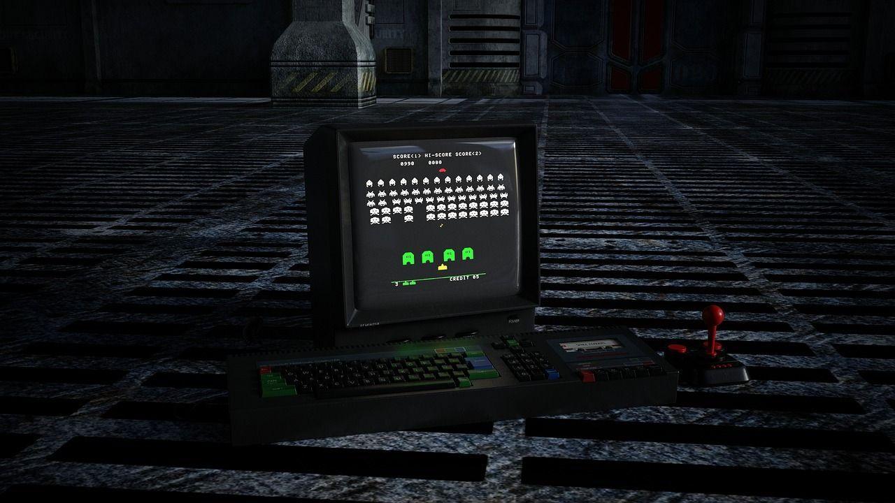 Una pc con teclado, joystick y en la pantalla se ve el juego Space Invaders
