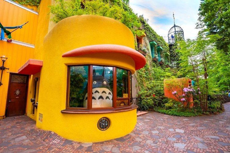 Imagen de la entrada al Museo de Ghibli en Mitaka, Tokio, con Totoro en la.cabina de recepción y a los lados vegetación.