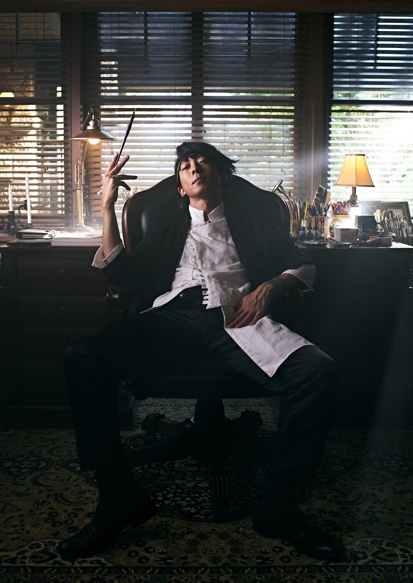 Imagen promocional de Kishibe Rohan wa Ugokanai con el protagonista sentado en un estudio