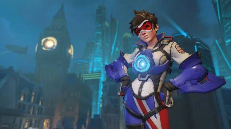 Un personaje de Overwatch 2 usando una armadura color blanco y morado y unos lentes rojos con las manos en las caderas y al fondo una ciudad vista en horas nocturnas.