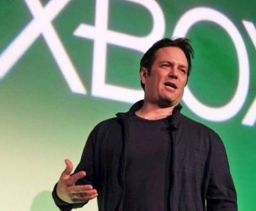 Phil Spencer presidente ejecutivo de Xbox un hombre con franela ychaqueta nega cabello negro corto dirigiéndose a un público
