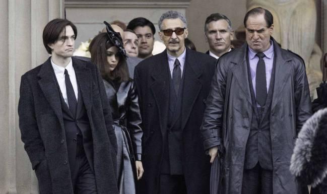 Grupo de personas vestidas de negro saliendo de funeral