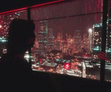Dr. DisRespect mirando a una ciudad iluminada en la noche, de espaldas a la cámara