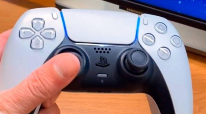 Un mando Dualnsense de color blanco con detalles negros sostenido por una mano en la que destaca un pulgar
