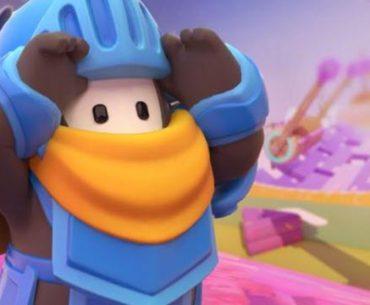 Un personaje de Fall Guys con armadura de caballero de color azul con un colorido escenario del juego al fondo