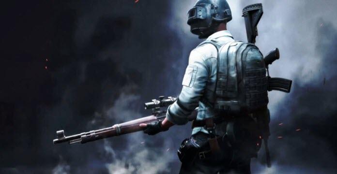 Un soldado sostiene un rifle de francotirador en sus manos mientras utiliza un casco de soldar. En su espalda luce una mochila y un rifle con un fondo oscuro y lleno de humo