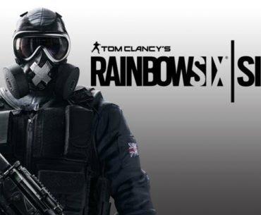 Un soldado con uniforme azul oscuro y un claleco antibalas y máscara antigás con el logo de Rainbow Six Siege en un fondo gris