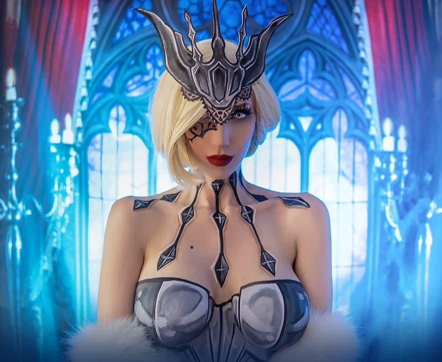 Fotografía de la cosplayer Intraventus haciendo la Signora de 'Genshin Impact' mientras mira a la cámara de forma seductora y al fondo se ve un ventanal lujoso.