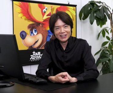 Masahiro Sakurai en un escritorio sonriendo al lado de un monitor