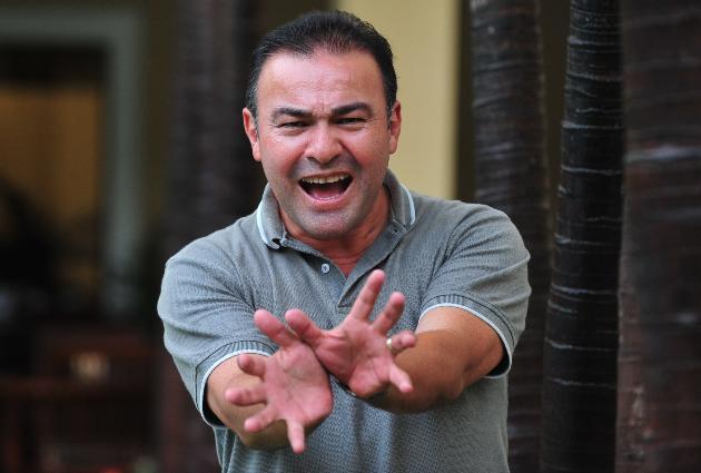 Fotografía de Mario Castañeda haciendo el Kame hame ha mientras al fondo se ve la entrada a una casa.