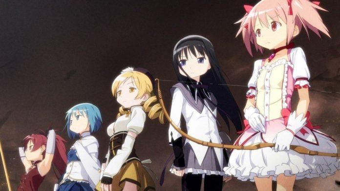 Imagen tomada del anime 'Mahou Shoujo Madoka★Magica' con toda las protagonistas aliniada en diagonal mirando hacia la izquierda en un fondo negro que se degrada a marrón de arriba hacia abajo.