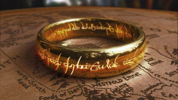 Imagen del anillo de Sauron con la frase iluminada en una mesa que tiene tallado un mapa de la tierra media.