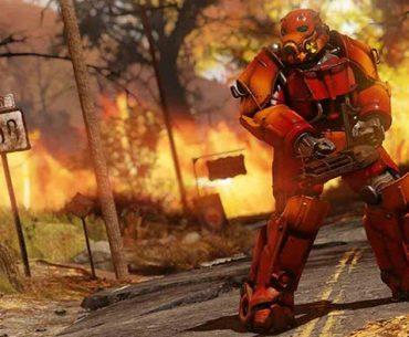 Un soldado con armadura roja sostiene su arma en medio de una calle con un incendio al fondo