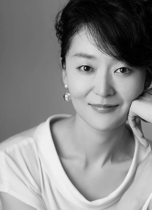 Fotografía en blanco y negro de Hikari Yono con una mano en su mejilla izquierda y sonriendo a la cámara
