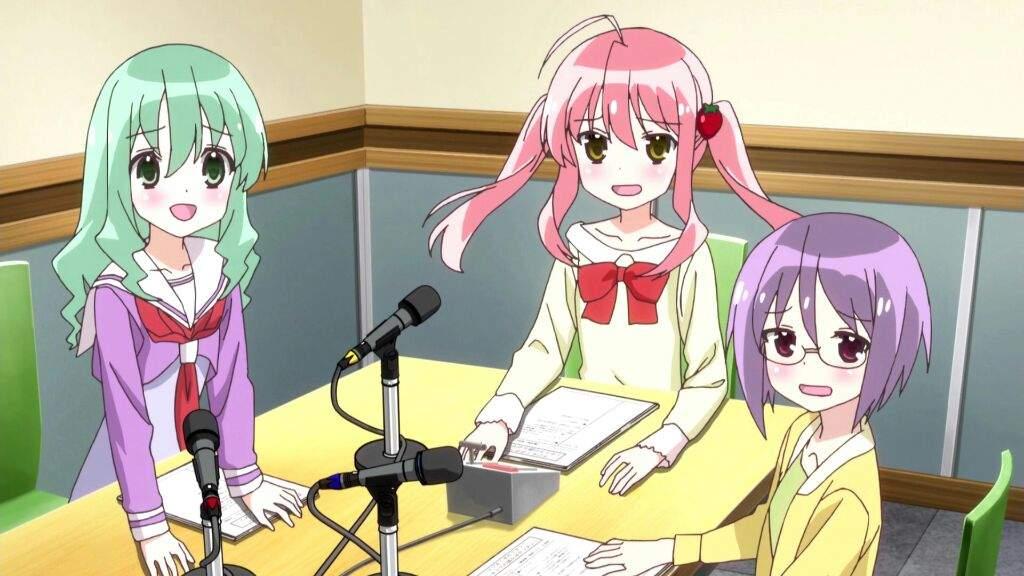 Imagen tomada de un anime donde tras chicas están sentadas frente a un micrófono para leer el guion.