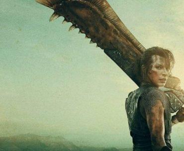 Imagen promocional de 'Monster Hunter' con Milla Jovovich de espaldas y mirando hacia la cámara mientras sostiene un arma de gran tamaño en su hombre y al fondo se ve un cielo en varios tonos de verde.