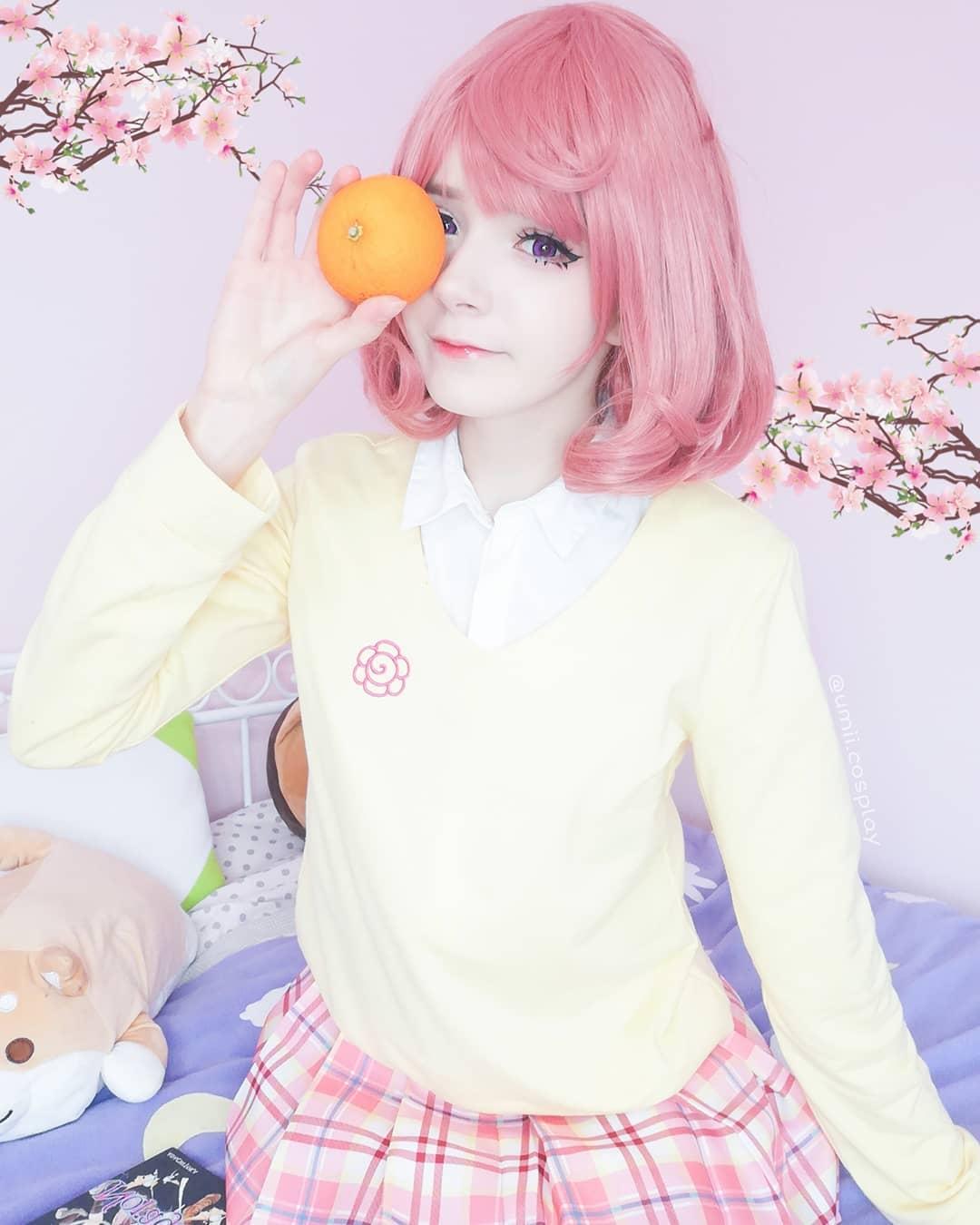 Fotografía de la cosplayer Umii haciendo de Kofuku de Noragami mientras sostiene una mandarina en su ojo derecho y al fondo se ve una cama con peluches y una pared en color rosa.