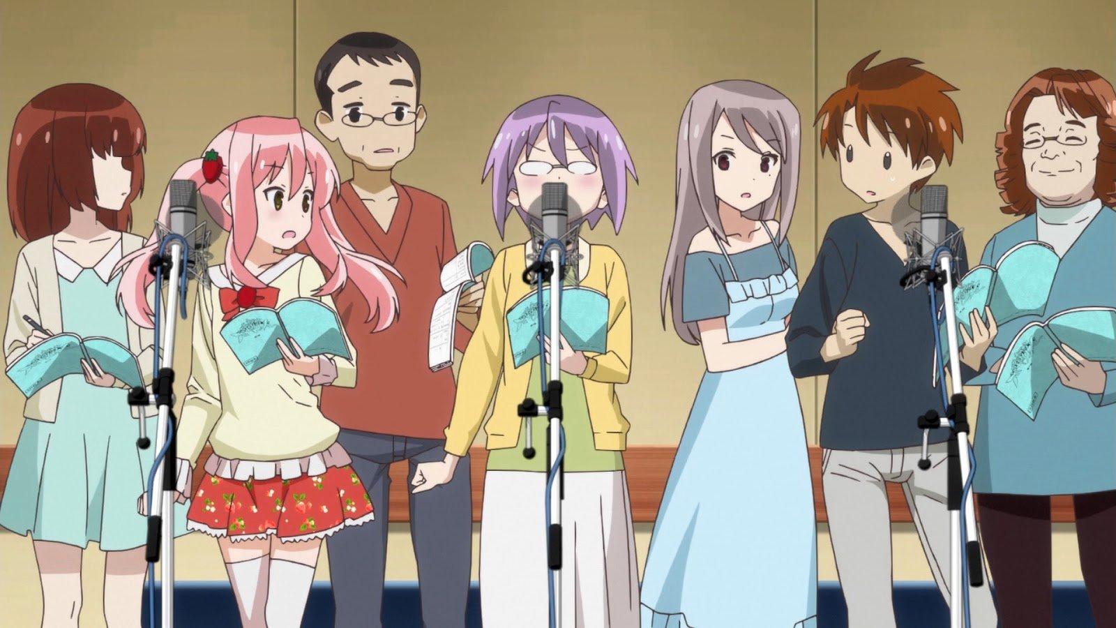 Imagen tomada de un anime donde varias personas están paradas frente a tres micros microbios mientras leen un guion y al fondo se ve una pared de color mostaza.