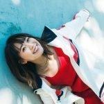 Fotografía de Shuka Saito mientras se inclina a la derecha en un pared de color azul cielo.