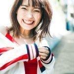 Fotografía de Shuka Saito sonriendo a la cámara con sus manos unidas mientras al fondo se ve una calle.