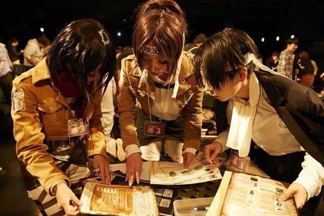 Fotografía tomada en el evento de escape real de 'Shingeki no Kyojin' con tres jugadores frente a una mesa llena de mapas y tableros mientras están en cosplays de personajes de la serie.