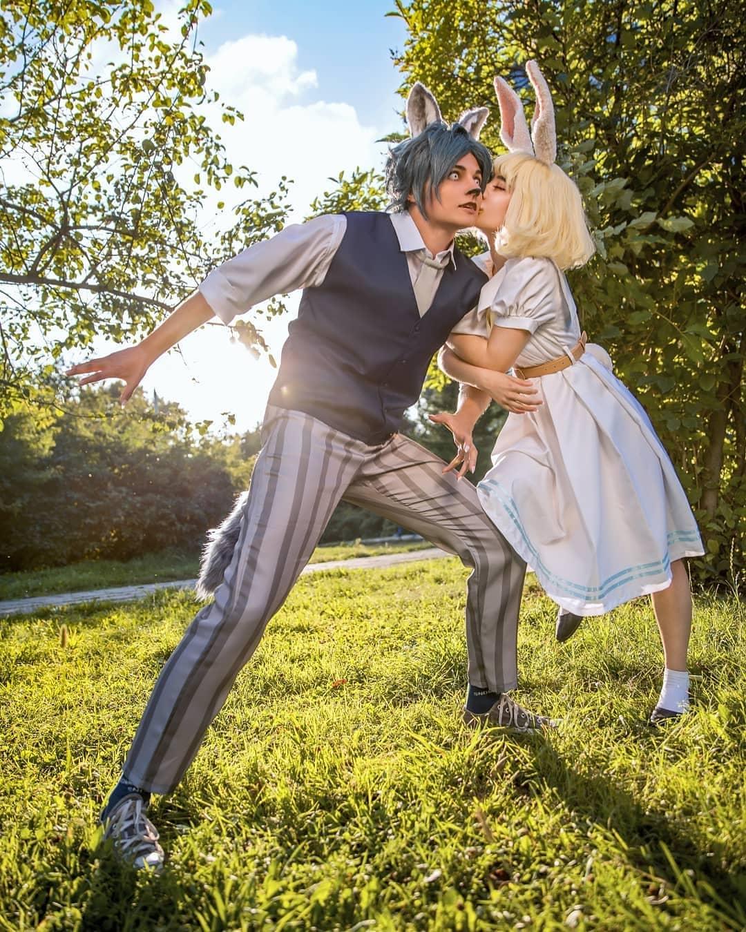 Fotografía de los cosplayers Ayame y Diana Schrader haciendo de Haru y Legoshi de 'Beastars' mientras ella lo besa en la.mejilla y lo toma del brazo izquierdo y al fondo se ve el parque y el cielo azul.