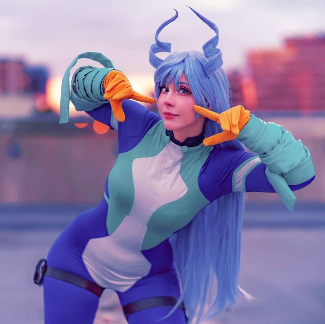 Fotografía de la cosplayer Mangoe haciendo de Nejire mientras posa para la cámara con sus dedos en sus mejillas y al fondo se ven los topes de los edificios.