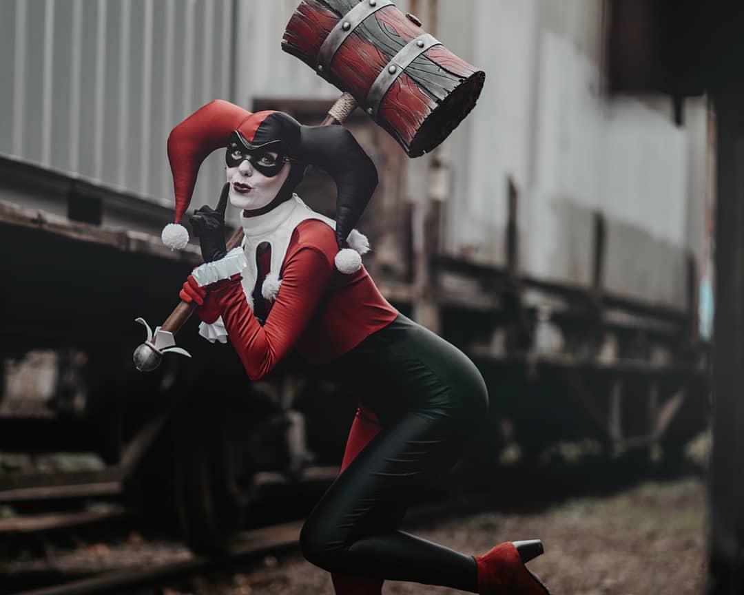 Fotografía de la cosplayer Zwillings Haciendo de Harley Quinn mientras sostiene el maso y mira la camara.