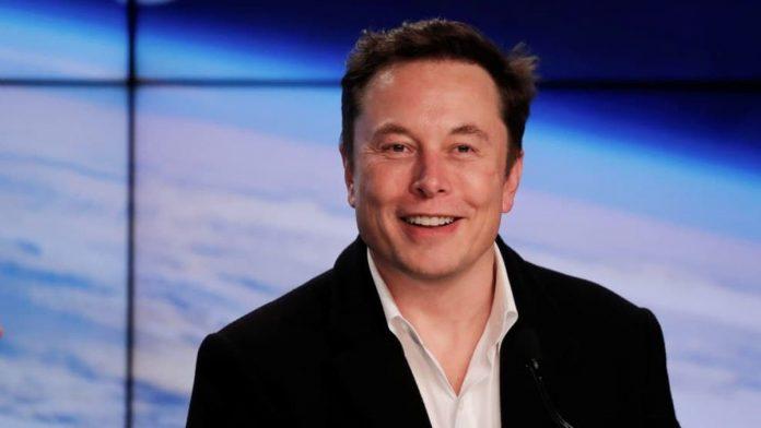 Fotografía de Elon Musk mirando hacia la cámara y la tierra al fondo.