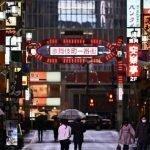 Fotografía de Tokio con rascacielos y parejas cumpliendo el distanciamiento social.
