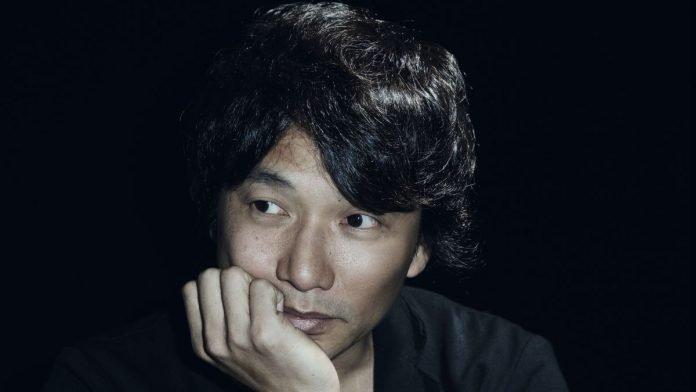 Fotografía bde Fumito Ueda el creador del juego 'The Last Guardian' en un primer plano mientras apoya su mejilla en su mano derecha en un fondo negro.