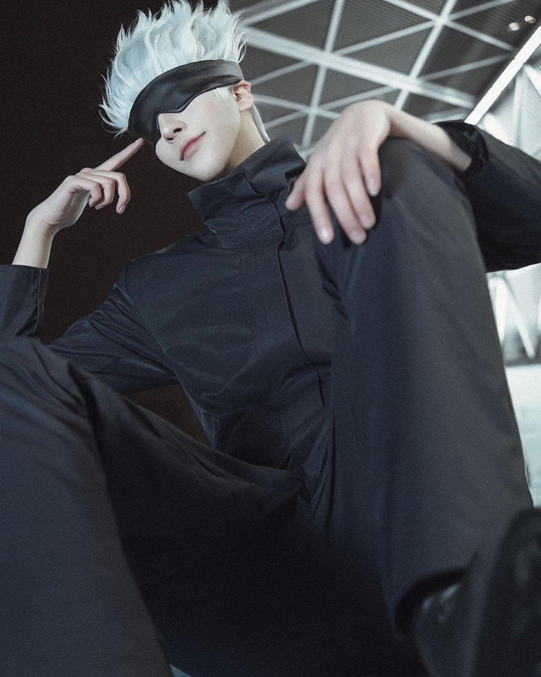 Fotografía del cosplayer Yuuji haciendo de Gojo de 'Jujutsu Kaisen' desde un pma o bajo en el que se le.ve sentado y mirando en dirección a la cámara.