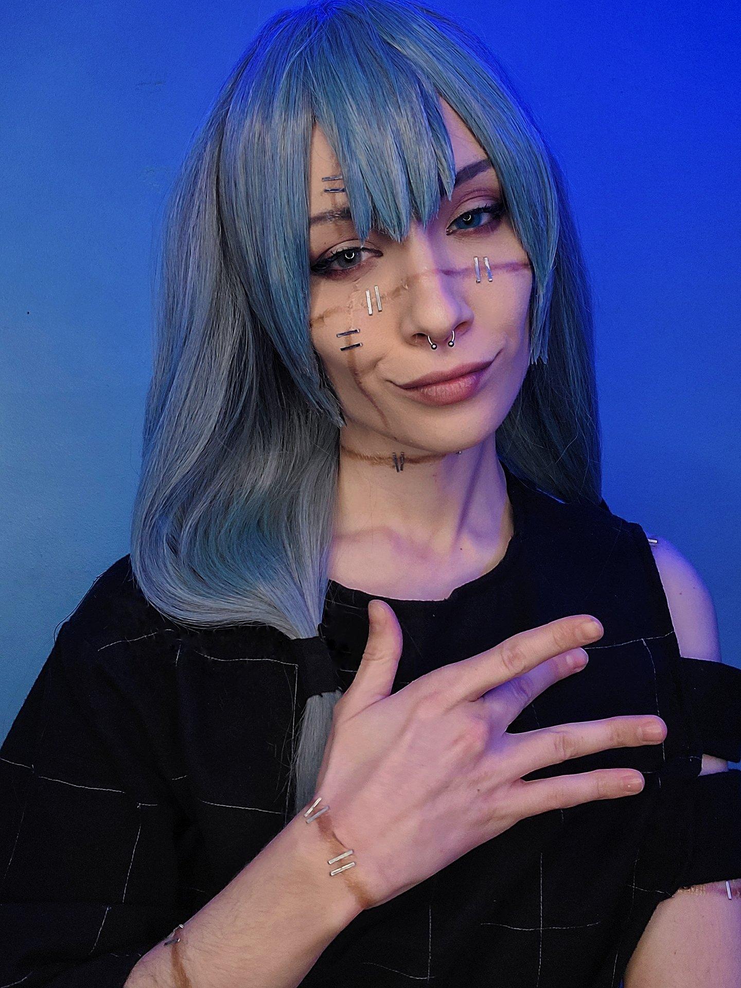 Fotografía de la cosplayer Nat haciendo de Mahito de 'Jujutsu Kaisen' mirando hacia la cámara con una sonrisa en el rostro en un fondo azul.