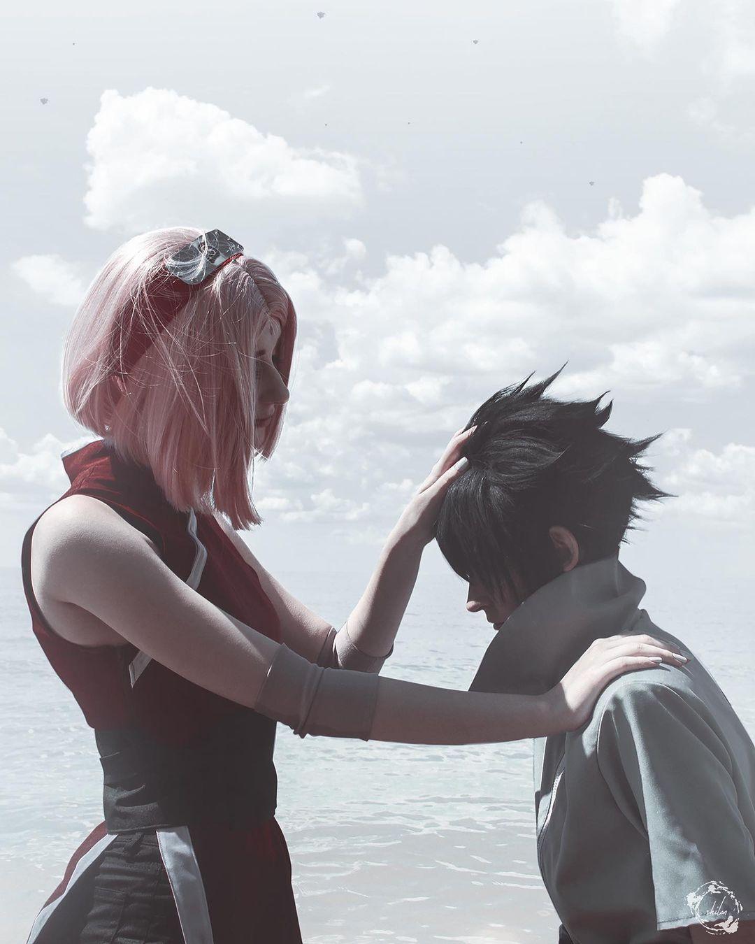 Fotografía de los cosplayers zerfika_natsuki y Jeong Eunho haciendo Sakura y Sasuke mientras ella le toca el cabello y al fondo se ve al mar.de