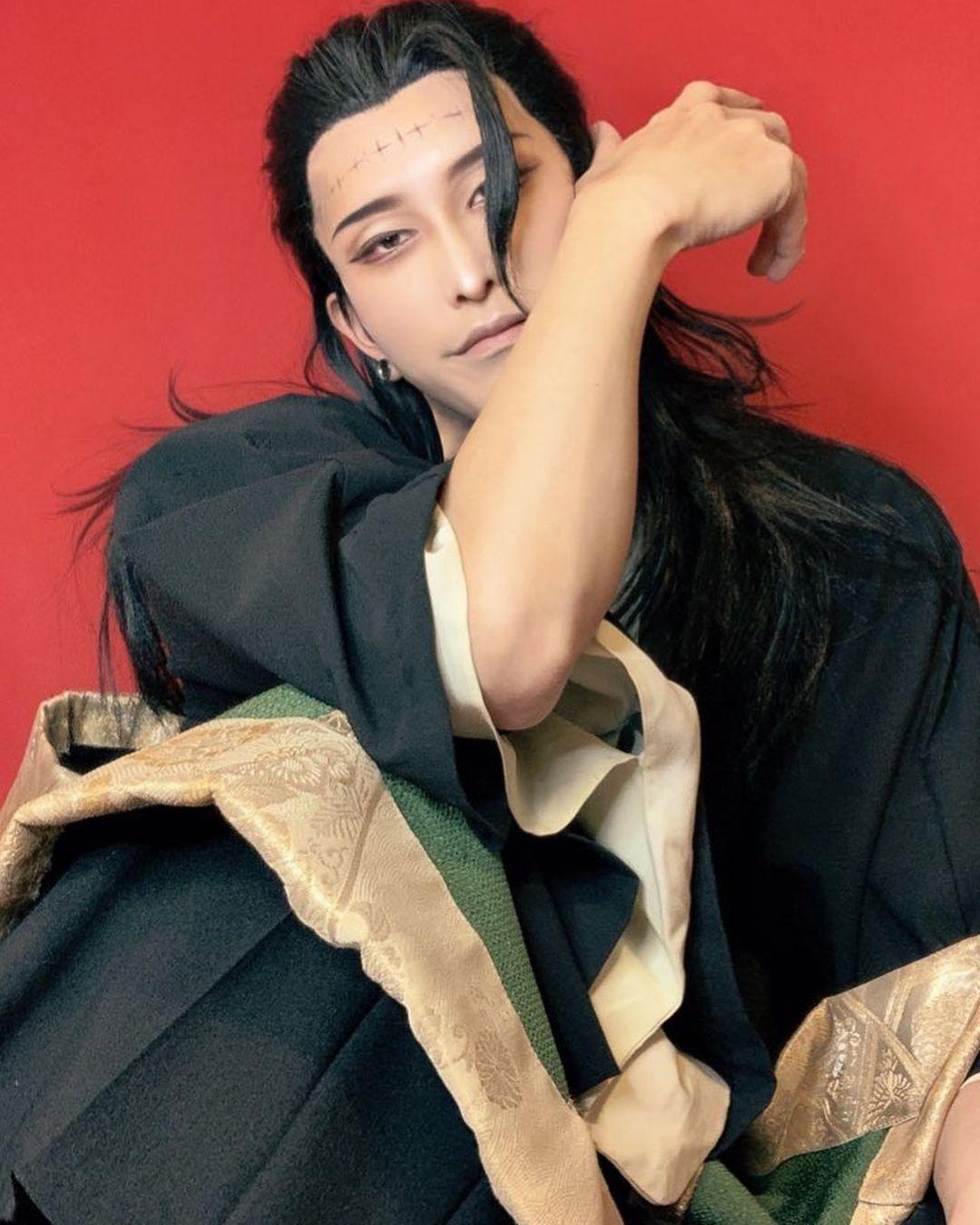 Fotografía del cosplayer Zumi haciendo de Suguru Geto de 'Jujutsu Kaisen' mientras está sentado en el sueño con expresión seductora en un fondo rojo.