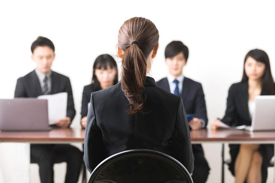 Imagen de un grupo de personas entrevistando a una mujer japonesa.