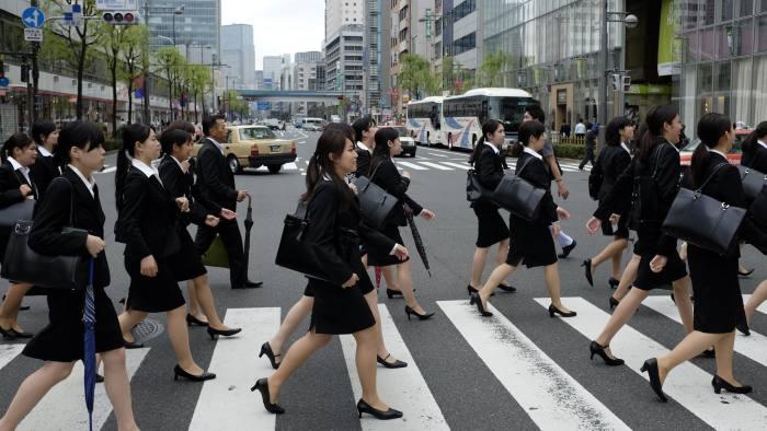 Fotografía de mujeres oficinistas japonesas cruzando un paso peatonal.
