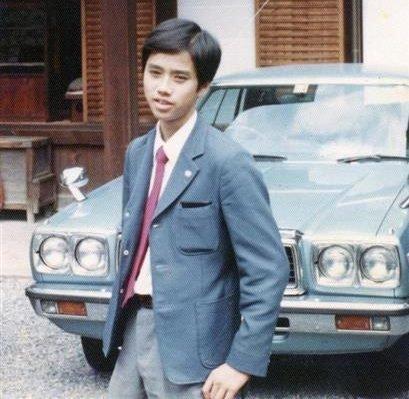 Foto juvenil de Satoshi Tajiri, utilizando un traje formal frente a un automóvil