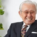 Fotografía de Shūichirō Moriyama sonriendo a la cámara en un fondo blanco con plantas a un lado.