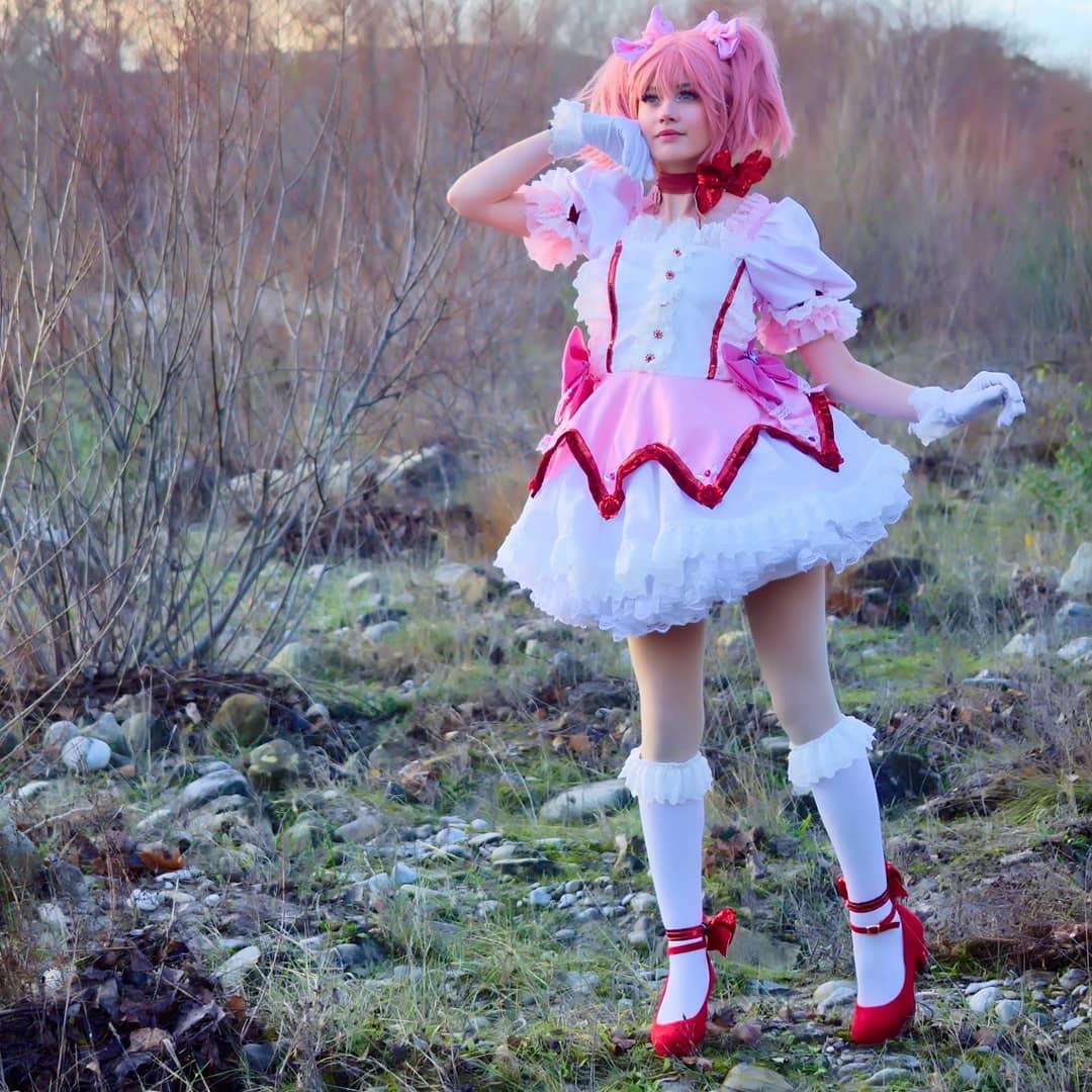 Fotografía de la cosplayer Betachuu haciendo de Madoka Kaname de 'Magia Record Mahou Shoujo Madoka Mágica Gaiden' posando con su mano derecha posada en su mejilla en un campo abierto.