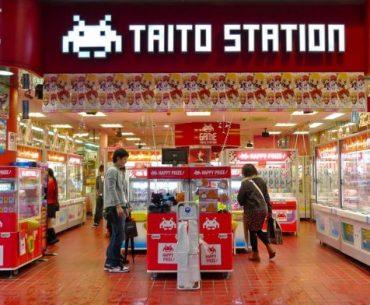 Entrada de la sala de arcades Taito Station de Shinjuku, con dos personas entrando y viendo los juegos y mercancía disponible