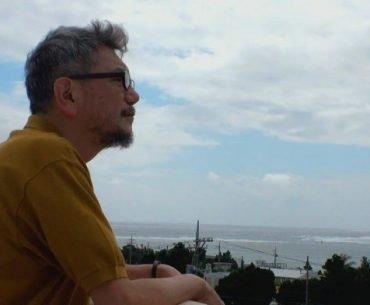 Foto de Hideaki Anno mirando de perfil hacia el mar