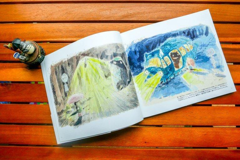 Fotografía de las ilustraciones en el libro de Akemi Ota sobre una mesa de madera.