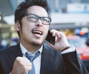 Salaryman japonés celebrando por teléfono en la calle