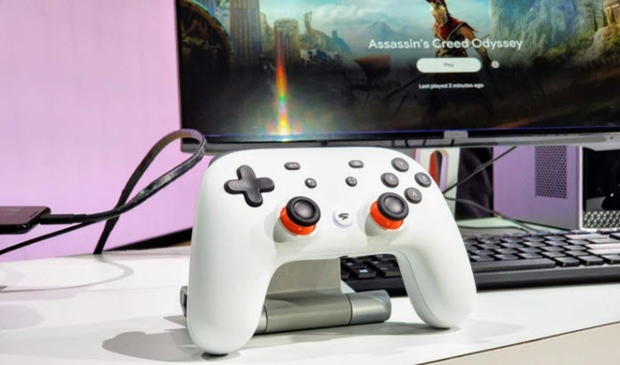 Mando de Google Stadia con un monitor al fondo con Assassin's Creed Oddysey