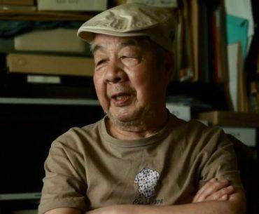 Fotografía de Yasuo Otsuka con los brazos cruzados en su oficina.